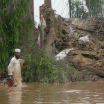 Ein Mann steht in den Fluten vor den Trümmern eines Hauses