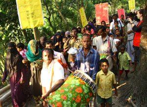 Mit Trommeln und Transparenten ziehen die Bewohner durch ihr Dorf