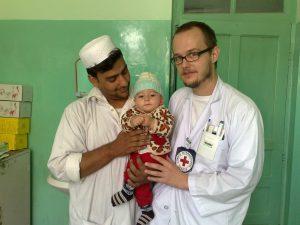 Krankenpfleger Ahmad Sabir, kleiner Patient und Christian Schuh auf der Kinderstation