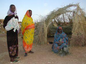Flüchtlinge vor ihrer Unterkunft in Darfur. (c)DRK/Heimendahl