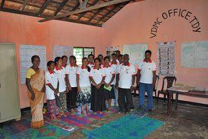 Ein Gruppe von Helferinnen und Helfern des Sri Lankanischen Roten Kreuzes hat sich in einem Raum mit Karten und Katastrophenvorsorgeübersichten aufgestellt.