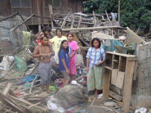 Eine Familie steht in den Trümmern ihres zerstörten Hauses.