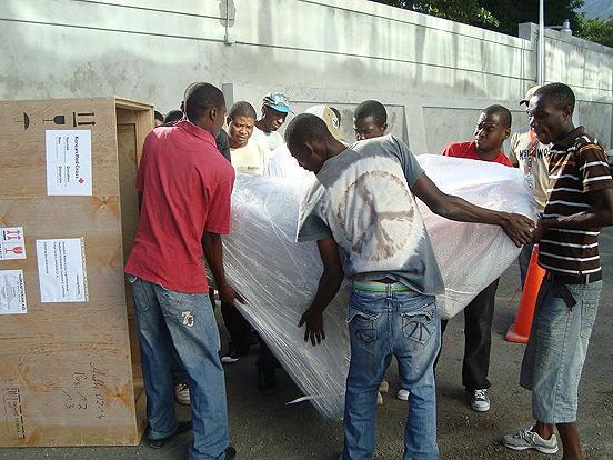 Mehrere Männer packen an, um die schweren Paletten auch ohne Gabelstapler zu bewegen