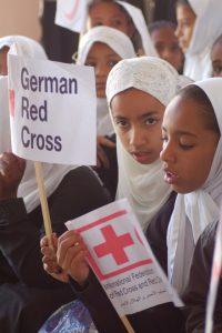 Zwei Schülerinnen in Tarim mit Rotkreuz-Flaggen