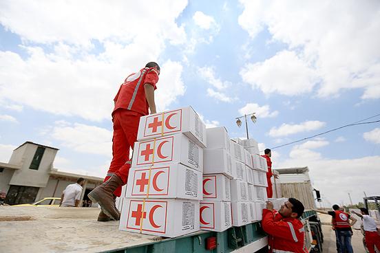 Freiwillige Helfer des Syrisch-Arabischen Roten Halbmonds entladen die Hilfsgüter.