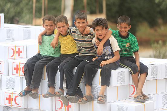 Syrische Kinder warten darauf eines der Hilfspakete mitnehmen zu dürfen. (Foto: © Ibrahim Malla/ IFRC)