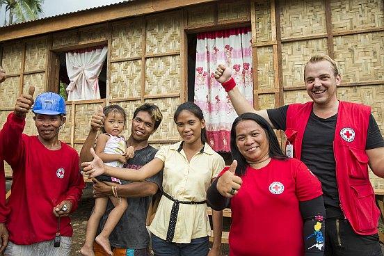 Eine philippinische Familie und DRK-Mitarbeiter Becker