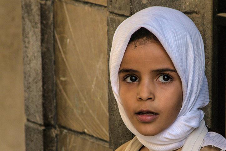 Foto eines jungen Mädchens vor einer Mauer