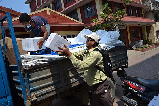 Hygienekits des DRK werden durch Mitarbeiter des Nepalesischen Roten Kreuzes aufgeladen. Projektleiter Philipp-Karl Gawel koordiniert die Hilfsaktion des DRK. Foto: René Schulthoff/DRK