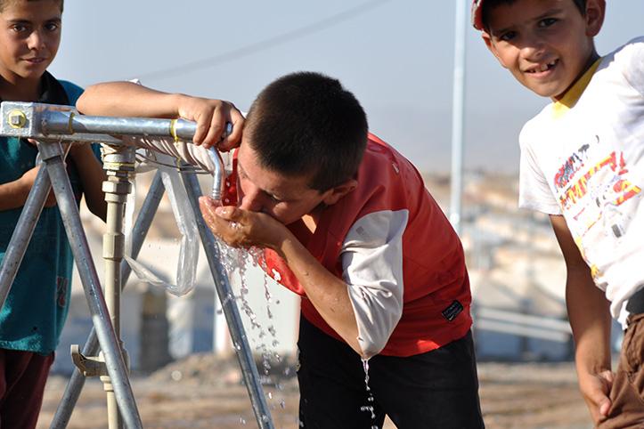 Foto: Junge trinkt an einer Wasserstelle