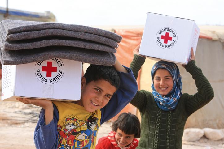 Foto: zwei syrische Kinder mit Hilfsgütern vom DRK