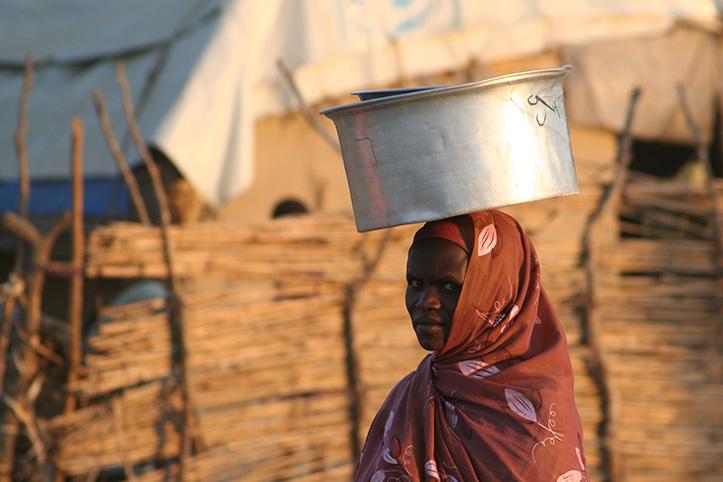 Foto: sudanesische Frau vor einer provisorischen Behausung