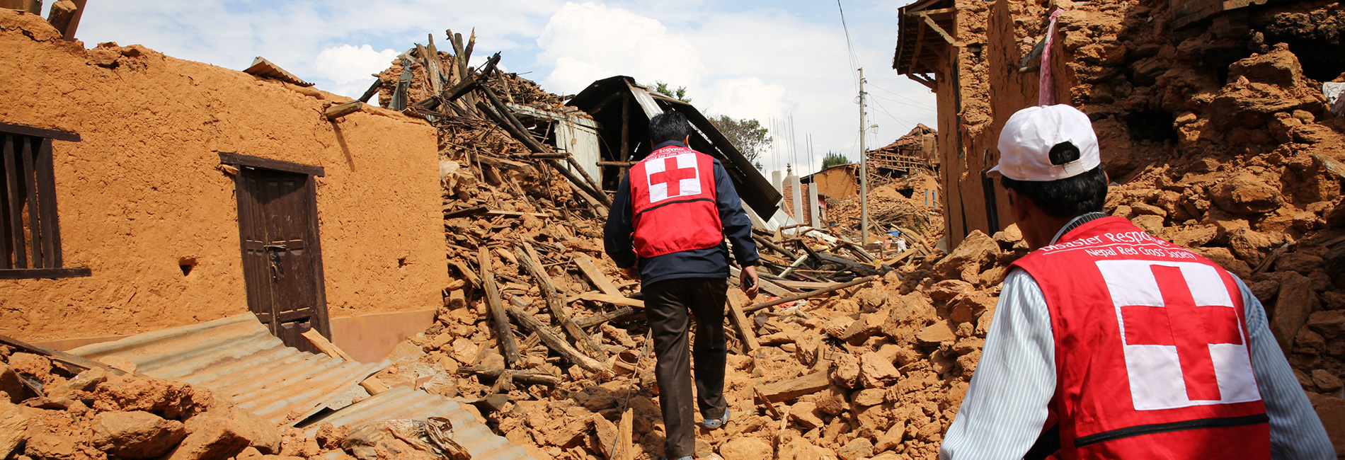 Foto: Nepalesische Rotkreuzhelfer laufen druch Trümmer.