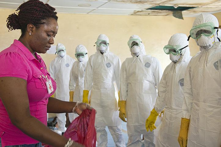 Foto: eine Liberianerin mit Personen in Ebola-Schutzanzügen