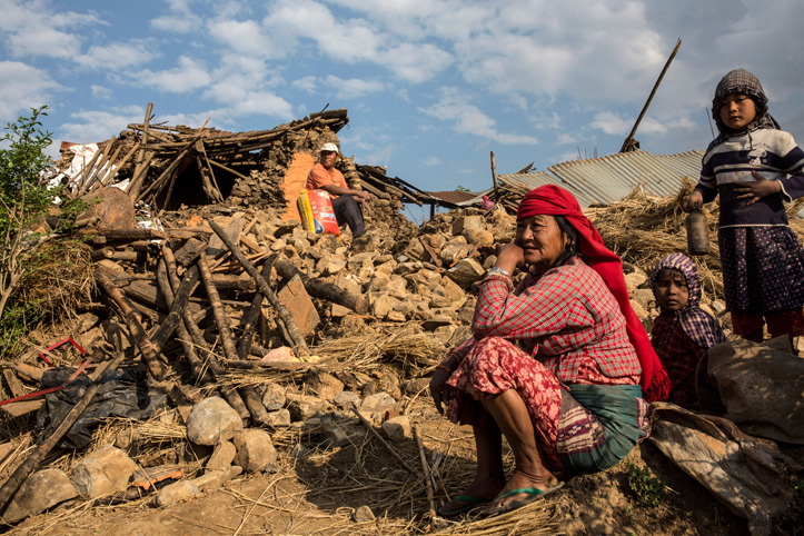 Foto: Eine ältere Frau und Kinder blicken auf die Trümmer in Nepal