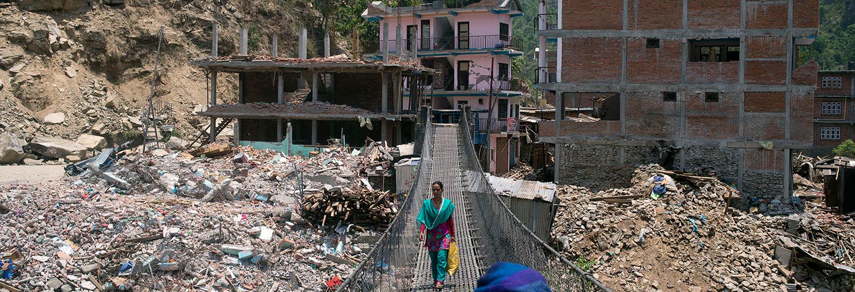 Foto: Eine Nepalesin läuft über eine lange Brücke
