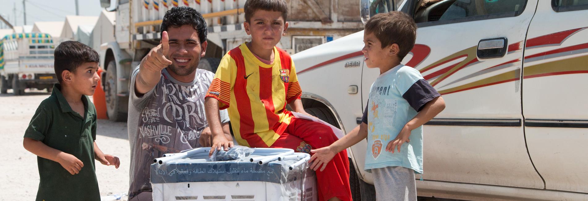 Foto: drei Jungen und ein junger Mann mit einem Luftkühler