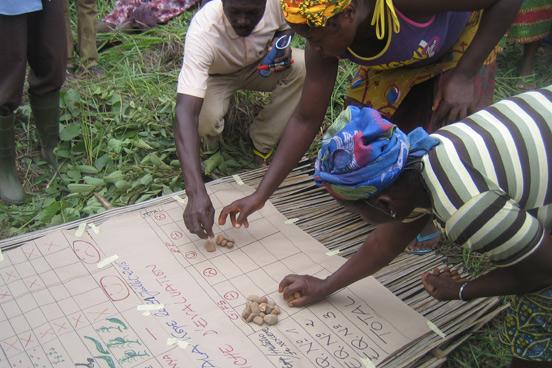 Foto: Frauen vergleichen anhand einer Kriterientabelle die Anbaumethoden.