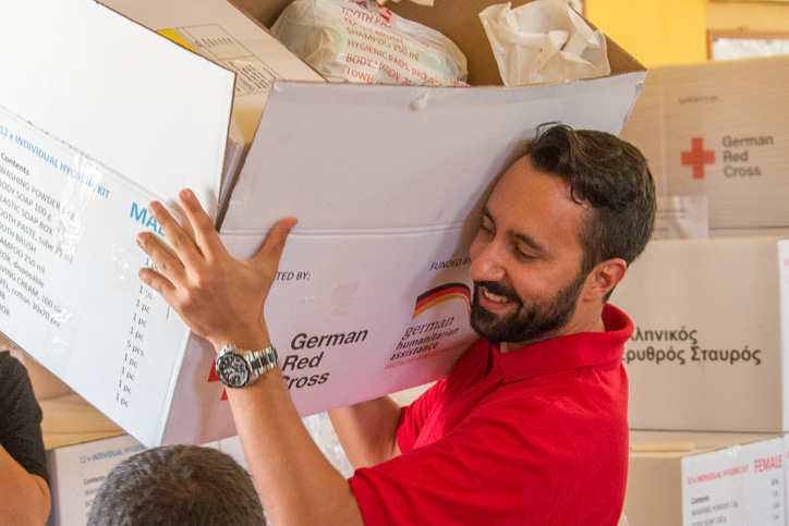 Foto: Ein Rotkreuzmitarbeiter trägt einen Kartom mit Hygienepaketen
