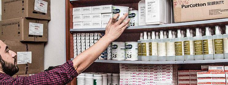 Foto: ein Mann greift in ein Regal mit Medikamenten und Babyzusatznahrung