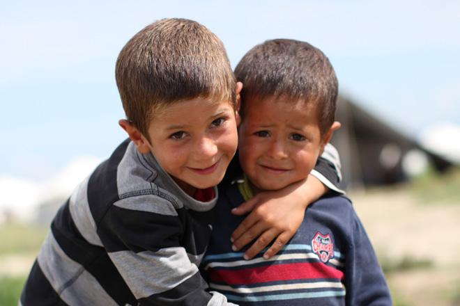 foto: zwei Flüchtlingskinder vor unterscharf zu erkennenden Zelten.