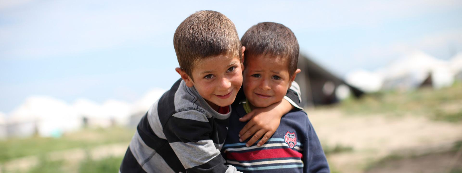 Foto: zwei Flüchtlingskinder vor unscharf zu erkennenden Zelten