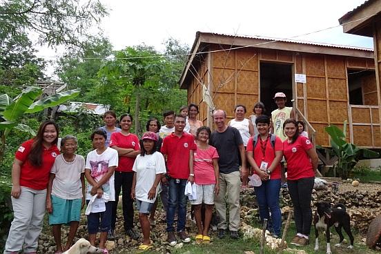 Das Rotkreuzteam vor einer der typischen Notunterkünfte aus Palmholz.