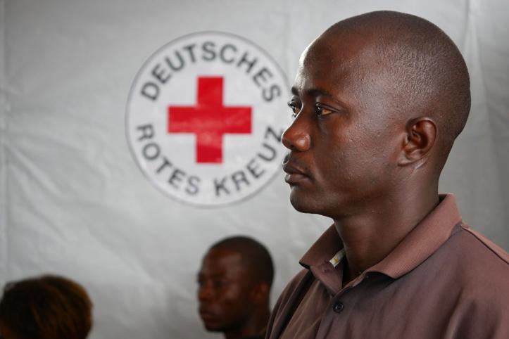Foto: Liberianischer Rotkreuzhelfer vor einem DRK-Logo
