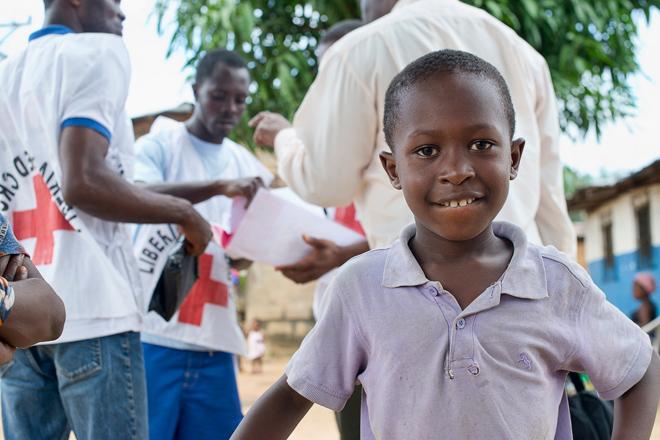 Foto: ein liberianischer Junge vor Rotkreuzhelfern