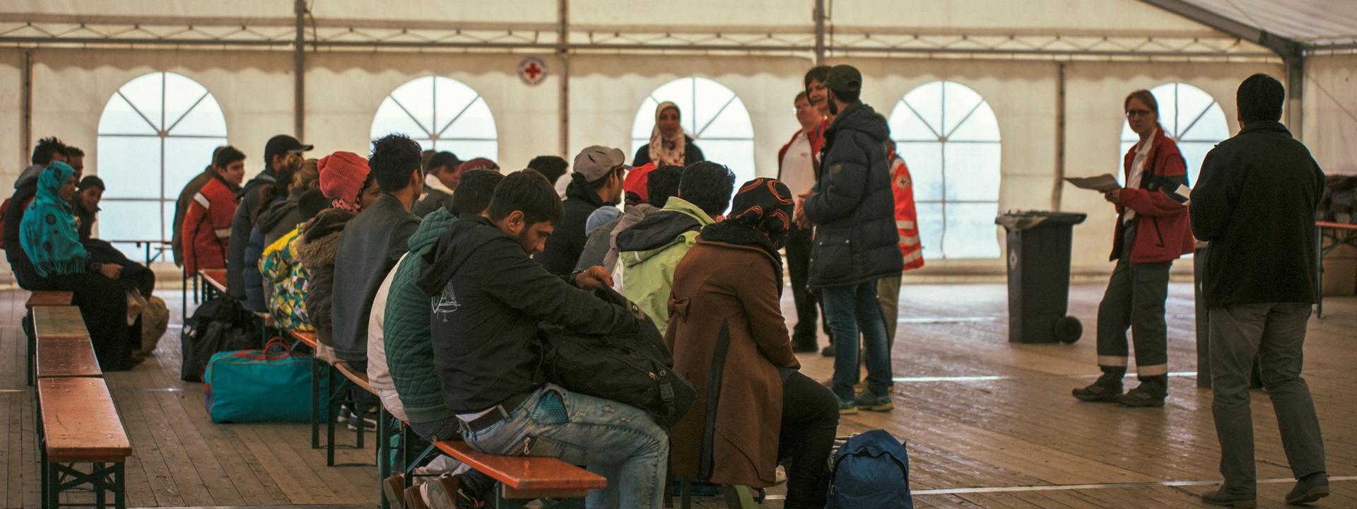 Foto: Flüchtlinge und Helfer in einem Zelt