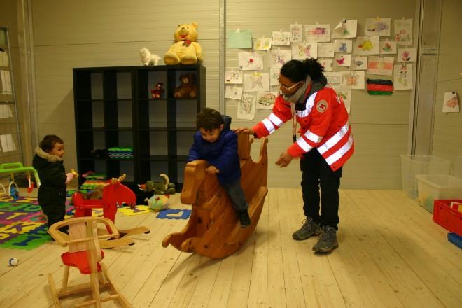 Foto: DRK-Helferin unterstützt ein Flüchtlingskind auf dem Schaukelpferd.