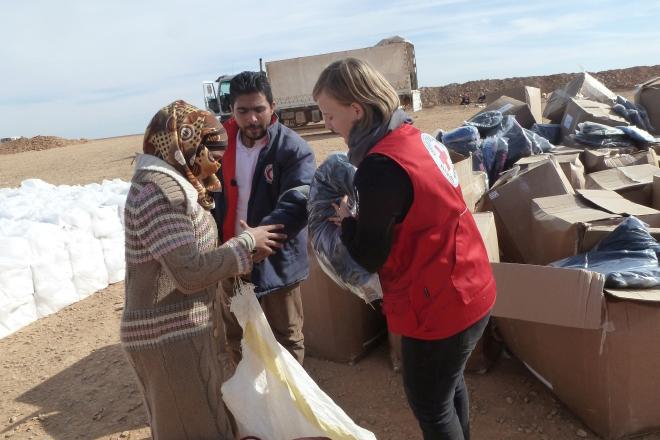 Foto: DRK-Mitarbeiterin übergibt Winterjacken an eine syrische Frau auf der Flucht.