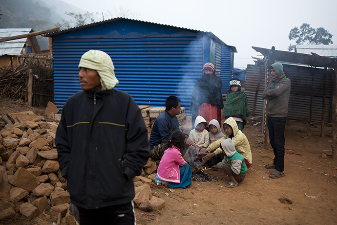 Eine Gruppe nepalesischer Menschen vor ihrer Notunterkunft