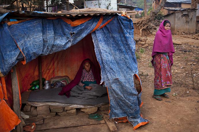 Eine nepalesiche Seniorin auf dem Boden ihrer notunterkunft aus Planen