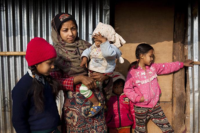 Eine junge nepalesische Mutter mit ihrem Kleinkind auf dem Arm