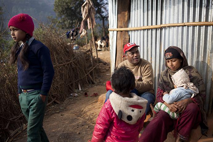 Menschen vor einer Notunterkunft mit einem Rotkreuzmitarbeiter