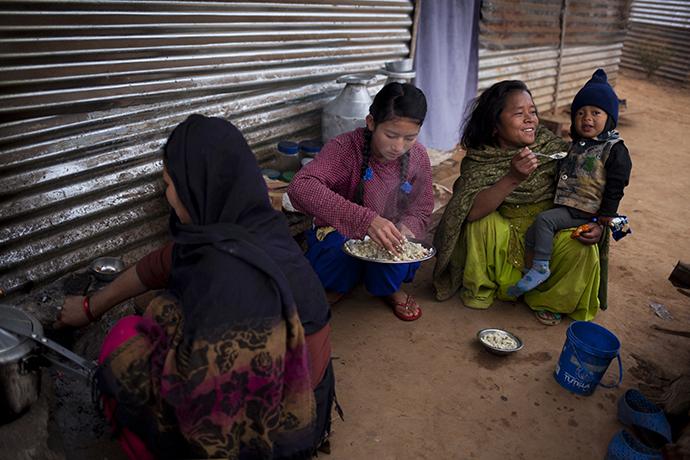 Eine nepalesische Familie isst Frühstück vor ihrer Notunterkunft