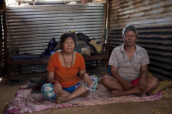 Ein nepalesisches Ehepaar auf dem Boden in ihrer Notunterkunft aus Wellblech