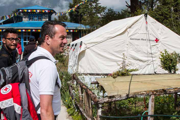 Foto: DRK-Delegierter vor einem DRK-Zelt in Nepal