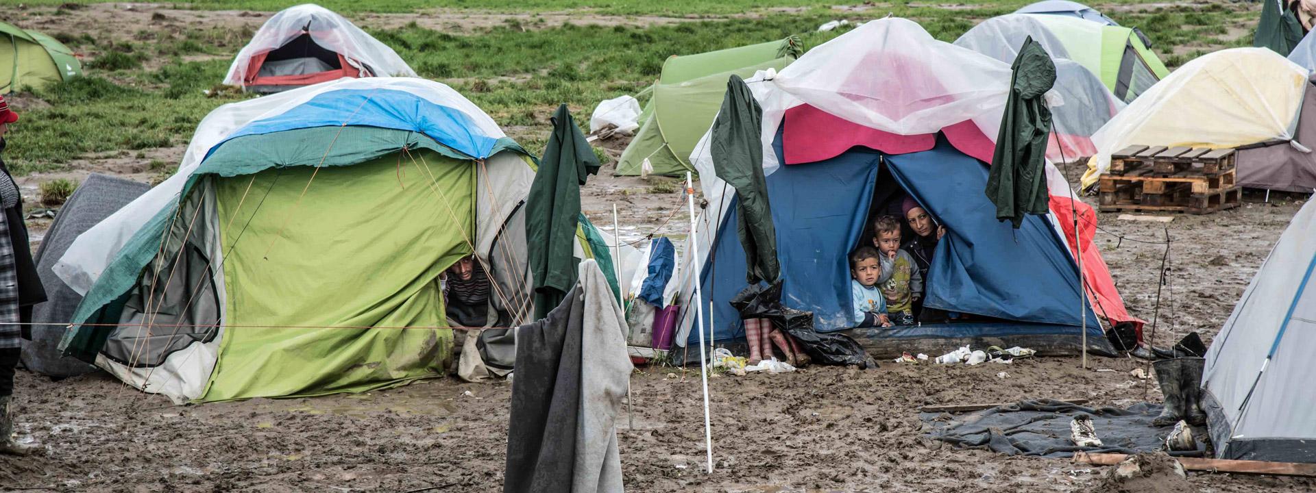 Foto: Flüchtlinge schauen in den Schlamm vor ihren Zelten.