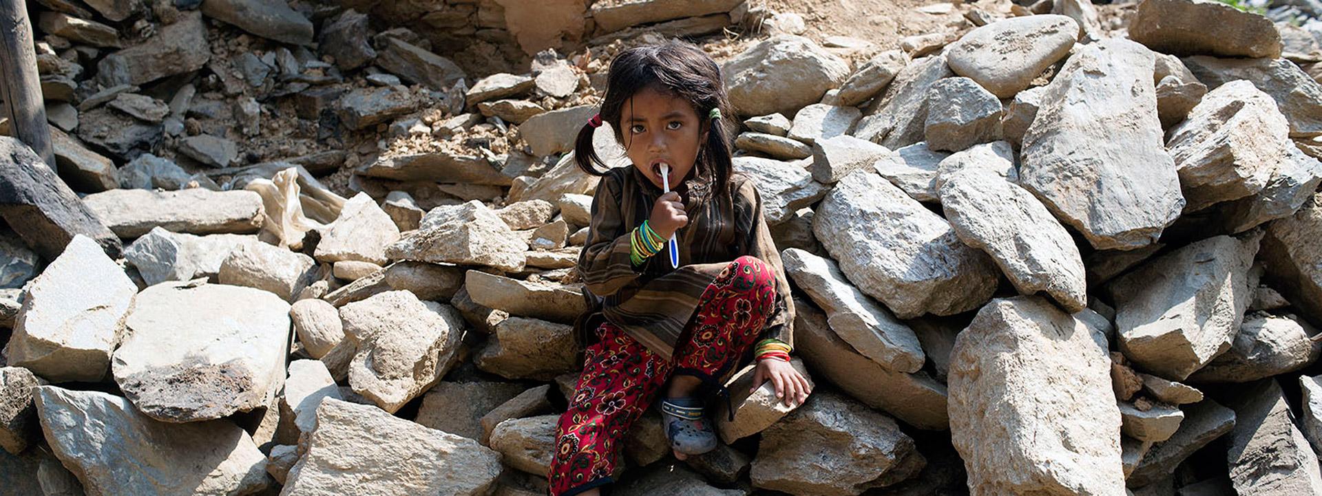 Foto: Ein nepalesisches Mädchen sitzt auf Trümmern.