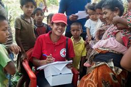 DRK-Mitarbeiterin umringt von nepalesischen Einwohnern