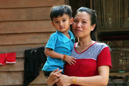 Foto: Mutter mit Kind auf dem Arm vor ihrem Haus in Laos