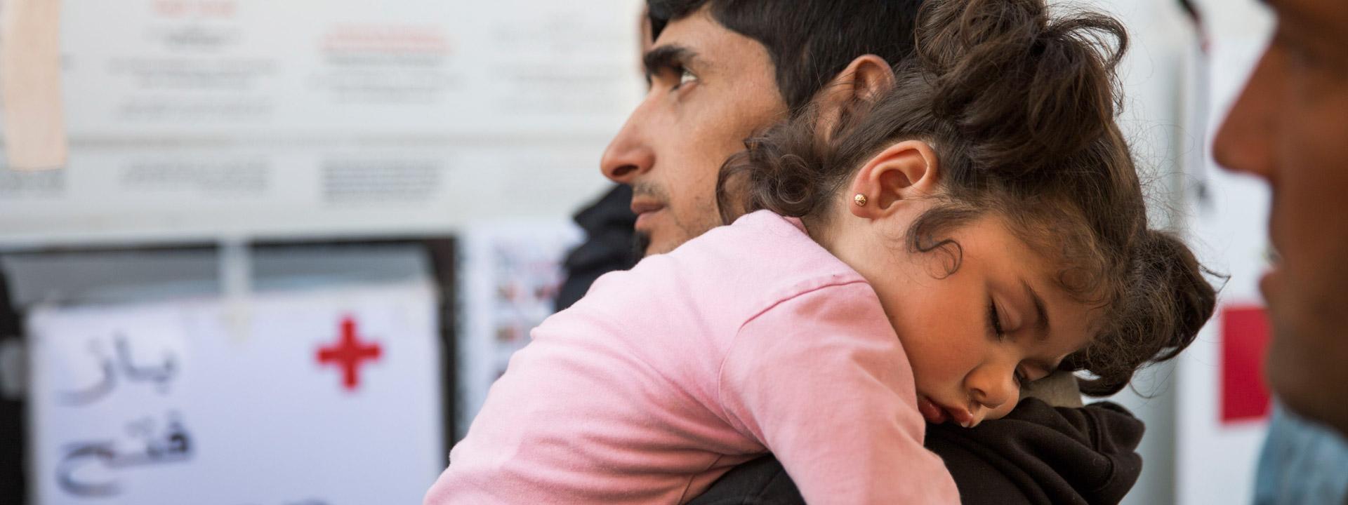 Foto: Ein geflüchteter Vater trägt seine schlafende Tochter.