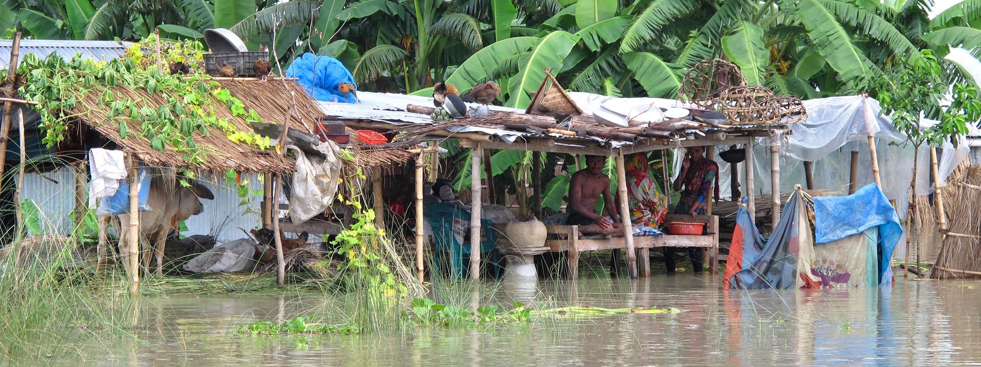 Foto: Menschen in überfluteten Bambusunterständen