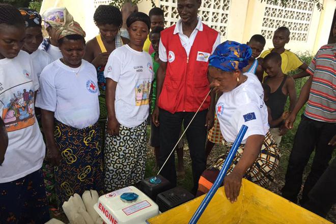 Foto: Eine togolesische Mutter wirft den Motor einer Maniokreibe an.