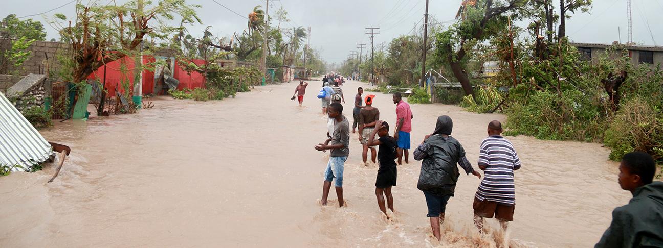 Foto: Menschen auf einer überfluteten Straße.