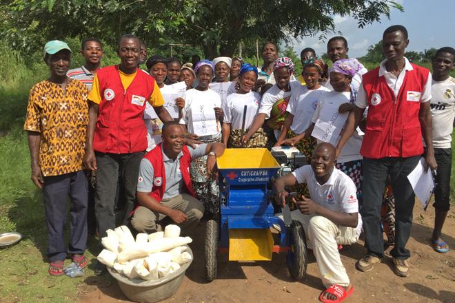 Foto: Eine Gruppe togolesischer Menschen um eine benzinbetriebene Maniokreibe.