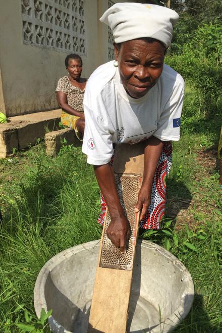 Foto: eine togolesiches Frau zeigt eine manuelle Maniokreibe.