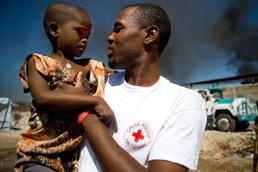 Foto: Haitianischer Rotkreuzhelfer hält ein Kind auf dem Arm.